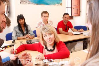 Učitelka angličtiny komunikuje se studenty jazykového kurzu v naší škole na Maltě