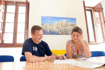 Učitel se věnuje studentce na soukromé hodině v jazykové škole