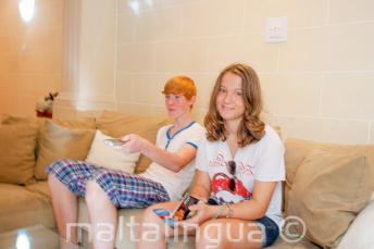 Studenti sedí na gauči v hostitelské rodině