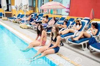 2 studentky si namáčejí nohy ve venkovním bazénu rezidence
