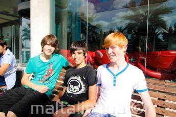 3 studenti sedí na lavici před rezidencí školy