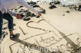 Student píše, I 'heart' Maltalingua, do písku