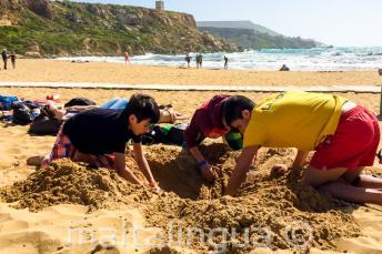 Vedoucí a studenti si hrajou na pláži v písku