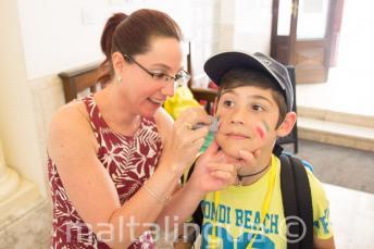 Zaměstnankyně maluje studentovi barvami na obličej