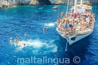 Studenti skákají z lodi do moře v Crystal Bay u ostrova Comino.