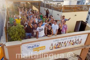 Studenti školy, mávají na střešní terase školy