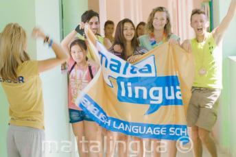Skupina studentů mává vlajkou na chodbě školy