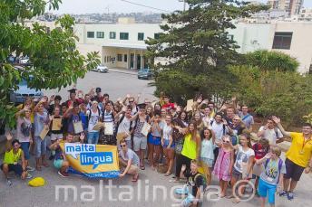 Velká skupina studentů mává před budovou letní školy