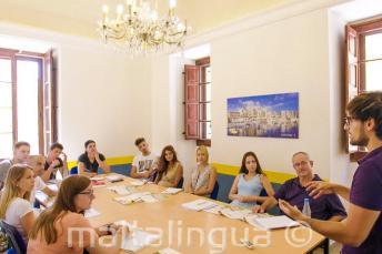 Studenti poslouchají učitele angličtiny v učebně jazykové školy