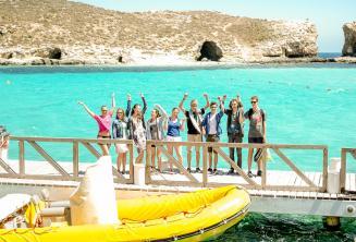 Skupina studentů mává vedle lodi v Blue Lagoon, Comino