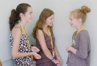 Studentky programu pro děti si povídají na chodbě školy