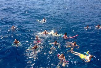 Velká skupina studentů plave společně v moři