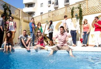 Studenti trávící volný čas u bazénu