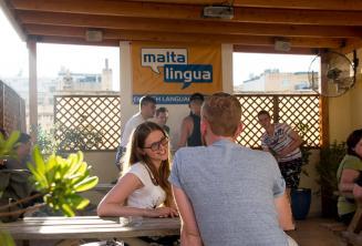 Studentka angličtiny si povídá se svým učitelem na terase školy