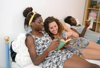 Studentka si čte knihu s jedním z členů rodiny
