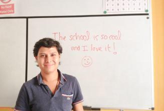 Student angličtiny, který právě napsal sprívně vzkaz na tabuli.